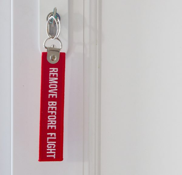 "Porte Clé tissu rouge 13cm ""REMOVE BEFORE FLIGHT"""
