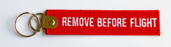 "Porte Clé tissu rouge 13cm ""REMOVE BEFORE FLIGHT"" vue face 1"